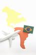 Trip by airplane to Brazil. Miniature airplane flies toward Brazil.