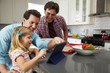 Girl using tablet in kitchen with male parents, close up