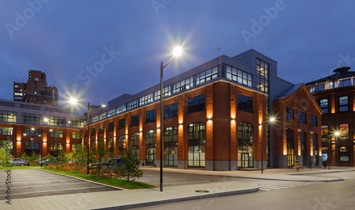 Extensive office complex exterior in loft style. Red brick buildings of former factory, gasholders. Evening architecture lighting, street lamps.