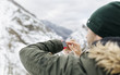 Spain, Asturias, young man using smartwatch in the snowy mountains
