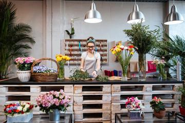 Nasmijana žena cvjećar stoji i radi u cvjećarni