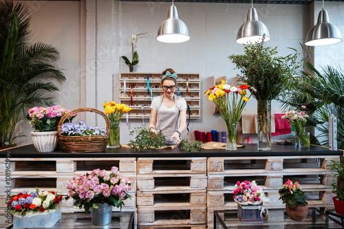 Uśmiechnięta kwiaciarni kobieta stoi i pracuje w kwiaciarni