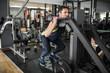 Senior man traning quadriceps and femoral muscle in gym, leg machine