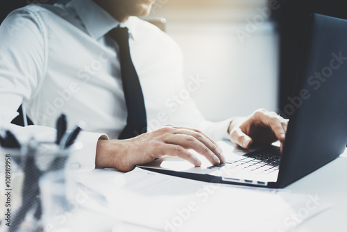 Fototapety, obrazy: Close-up of young businessman working at his modern office on laptop, successful employer using portable computer in interior, flare light
