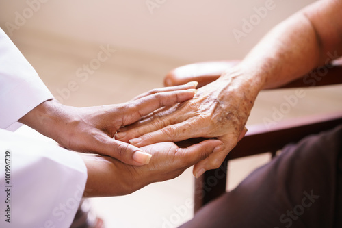 Senior Woman Talking With Black Doctor In Hospice Fototapeta