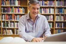 Portrait Of Happy Professor Sitting At Desk Using Laptop