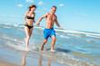 cute woman in bikini running on sunny beach hand in hand with man