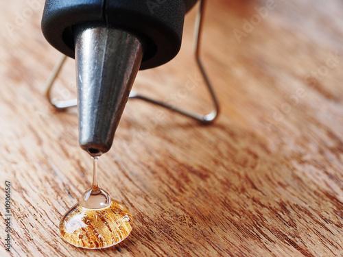 Obraz closeup hot glue gun with melted glue dripping out - fototapety do salonu