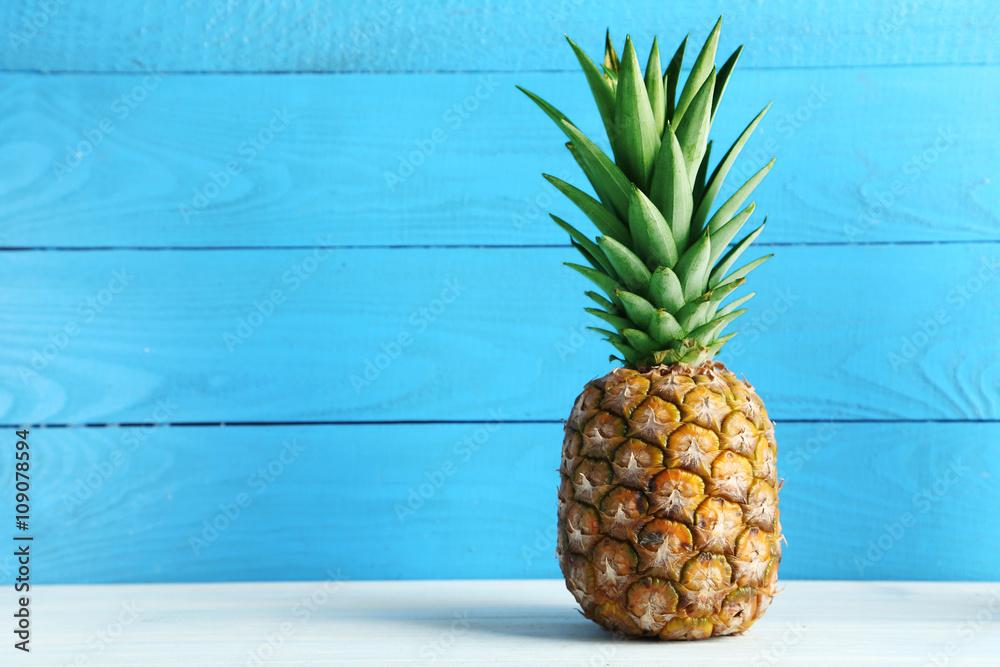 Fototapeta Ripe pineapple on a white wooden table