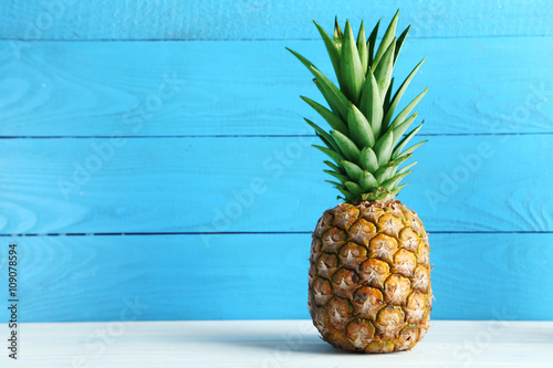 Ripe pineapple on a white wooden table Canvas Print