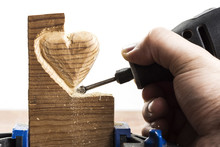 Carving Wood In Heart Shape With Rotary Tool, On White Background