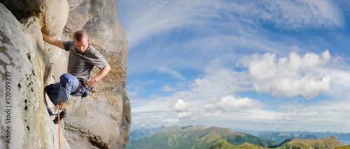 Fotografia, Obraz Strong male rock climber climbs with rope and carbines on multi-pitch against blue sky and scenic mountain background