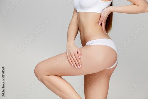 Fototapeta Slim tanned woman's body over gray background obraz na płótnie