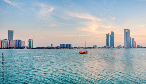 Photo  Cityscape of Abu Dhabi with a boat passing by, UAE