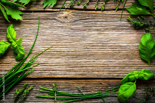 Fotografering Fresh herbs on wooden background