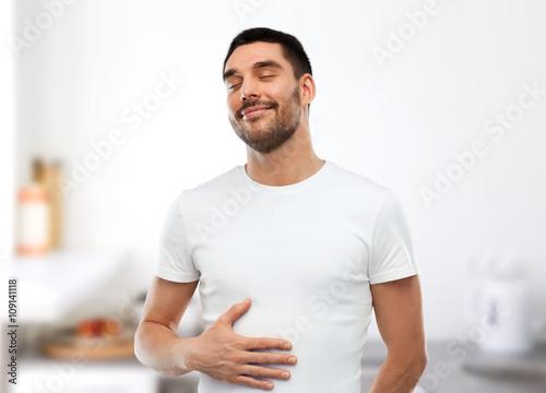 Fotografia  happy full man touching tummy over kitchen
