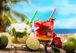 Mojito limea and strawberry drinks on wood with blur beach background