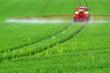 canvas print picture - Traktor mit Feldspritze beim Ausbringen von Pflanzenschutzmittel