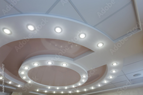 Layered ceiling with embedded lights and stretched ceiling inlay