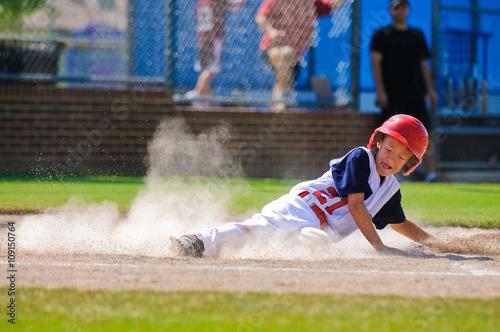 Little league baseball player sliding home.