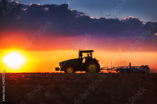 Leinwand Poster  Farmer in tractor preparing land with seedbed cultivator