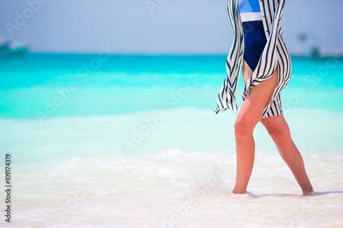 Fotografia, Obraz  Woman's feet on the white sand beach in shallow water