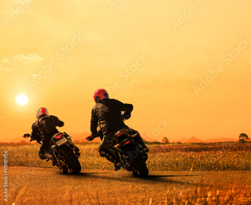 obraz lub plakat couples friend motorcycle rider biking on asphalt highway agains