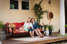 Mother With Daughters, Sitting On Porch Swing Looking At Camera Smiling