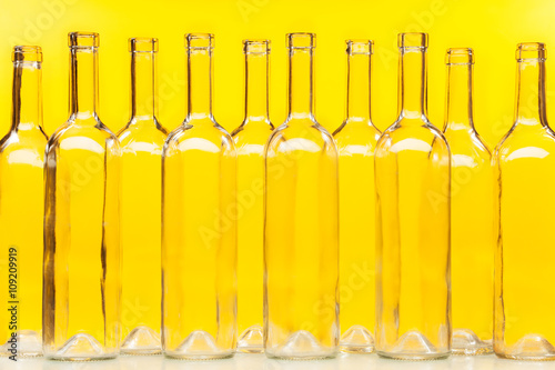 Fototapeta Empty transparent glass bottles over yellow wall