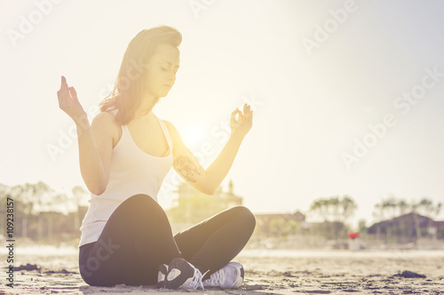 Young healthy woman practicing yoga on the beach Canvas Print