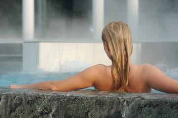 Obraz na płótnie Canvas Rückenansicht einer jungen blonden Frau bei einem Aufenthalt in der Rupertustherme Bad Reichenhall