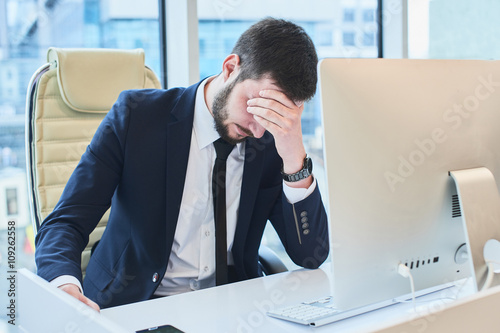 Photographie The guy sitting at the table and holding his head in the office