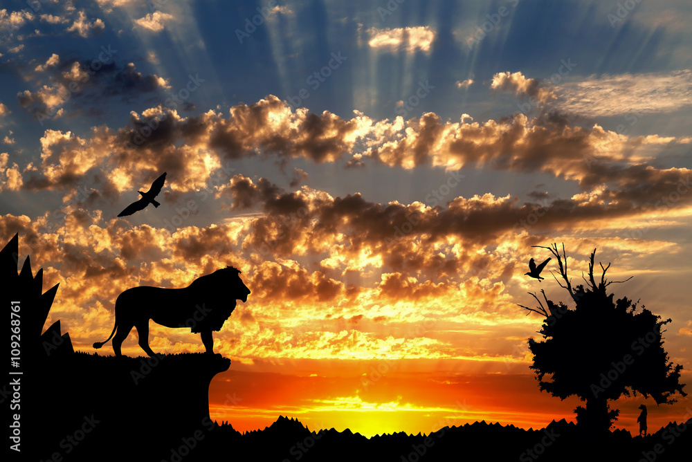 Fototapeta Jungle with mountains, old tree, birds lion and meerkat on golden cloudy sunset background
