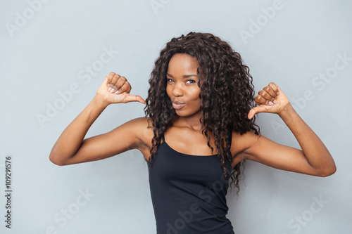 Fotografie, Obraz  Afro american woman showing fingers at herself