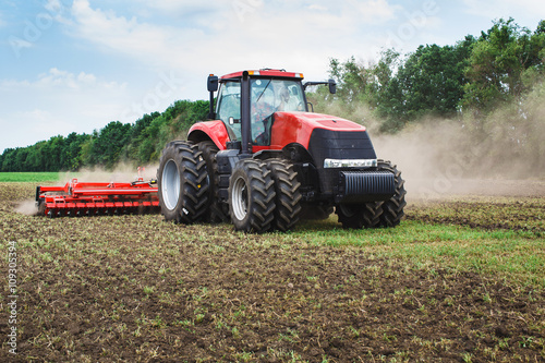 Modern tech red tractor plowing a green agricultural field in spring on the farm. Harvester sowing wheat.
