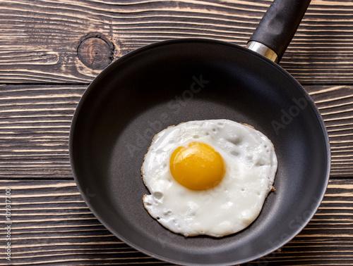 Cadres-photo bureau Ouf Fried sunny side up eggs on a pan on a brown oak old wooden board