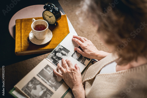 Valokuva an elderly woman looks at your picture in the album made many years ago