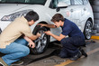 Customer And Mechanic Discussing Over Car Tire