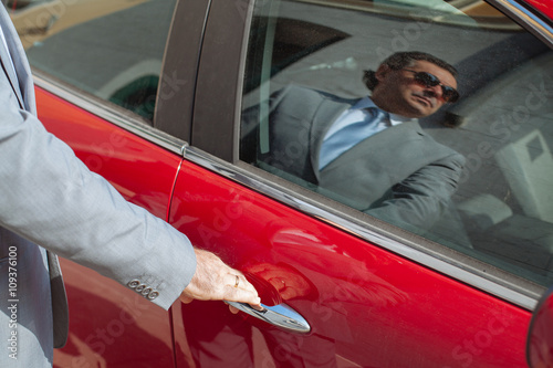 Successful businessman opens its luxury car red Canvas Print