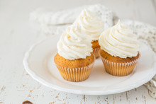 Vanilla Cupcakes On White Wood...