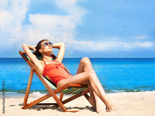 Young and sexy woman in a deckchair on the beach