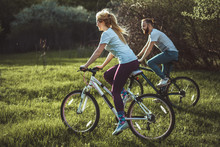 Beautiful Young Girl And Man Walking With A Bike Ride On The Green Grass. The Concept Of Active Rest