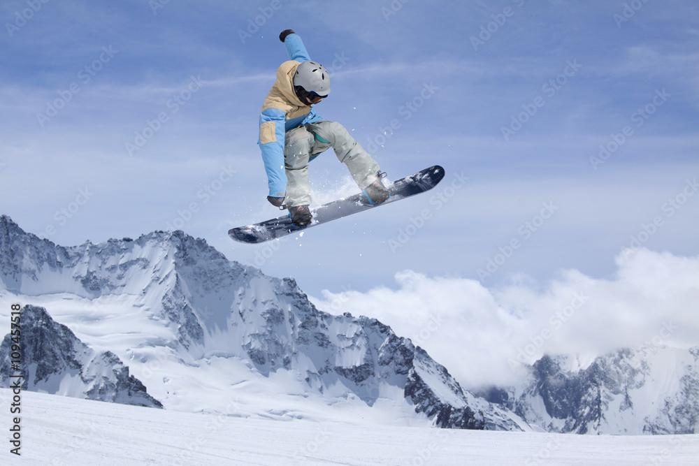 Fototapeta Na Wymiar Snowboard Rider Jumping On Mountains