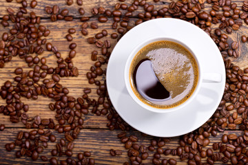 Fototapeta Do kawiarni cup of coffee with beans on wooden table