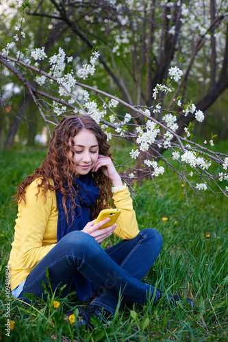 Photo  Beautiful young woman sitting on grass with a smartphone