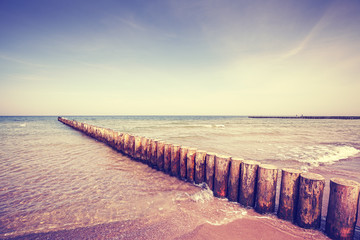 FototapetaVintage toned wooden breakwater on a beach