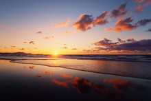 Sunset On Beach With Cloud Reflections