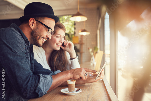Obraz Couple using a digital tablet at coffee shop - fototapety do salonu