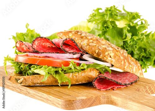 salami sandwich with full-corn bread on cutting board on white