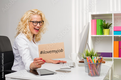 "Fotografía  Woman in office showing ""I love my job"" cardboard"
